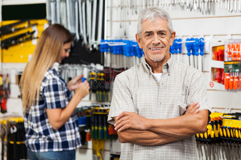 Confident Senior Man With Arms Crossed In Hardware royalty free stock photography