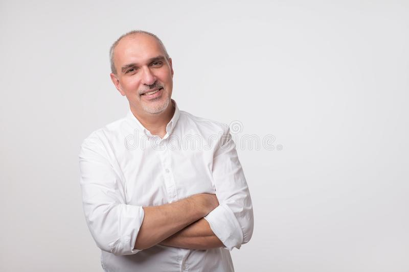 Confident senior man in white t-shirt crossing hands on chest and looking at camera stock photography