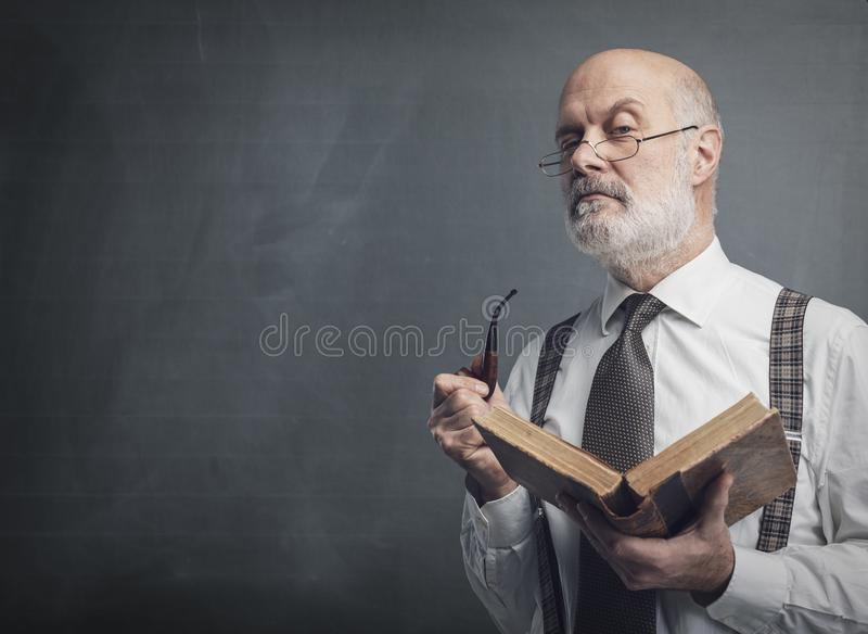 Senior academic professor reading and smoking a pipe. Confident senior professor smoking a pipe and reading an old book, knowledge and education concept royalty free stock photo