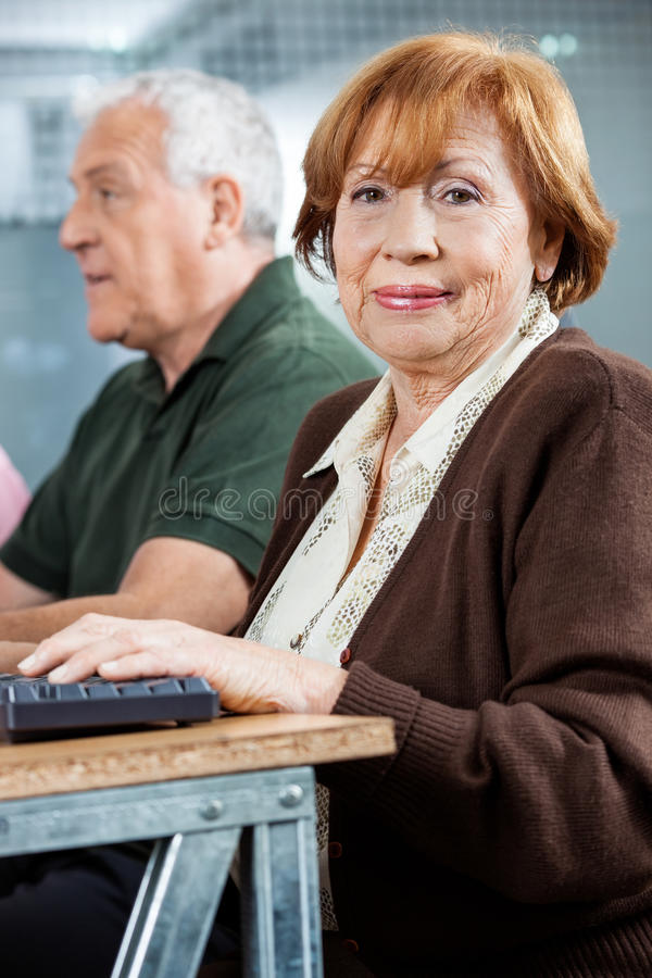 Confident Senior Student Sitting In Computer Class stock photo