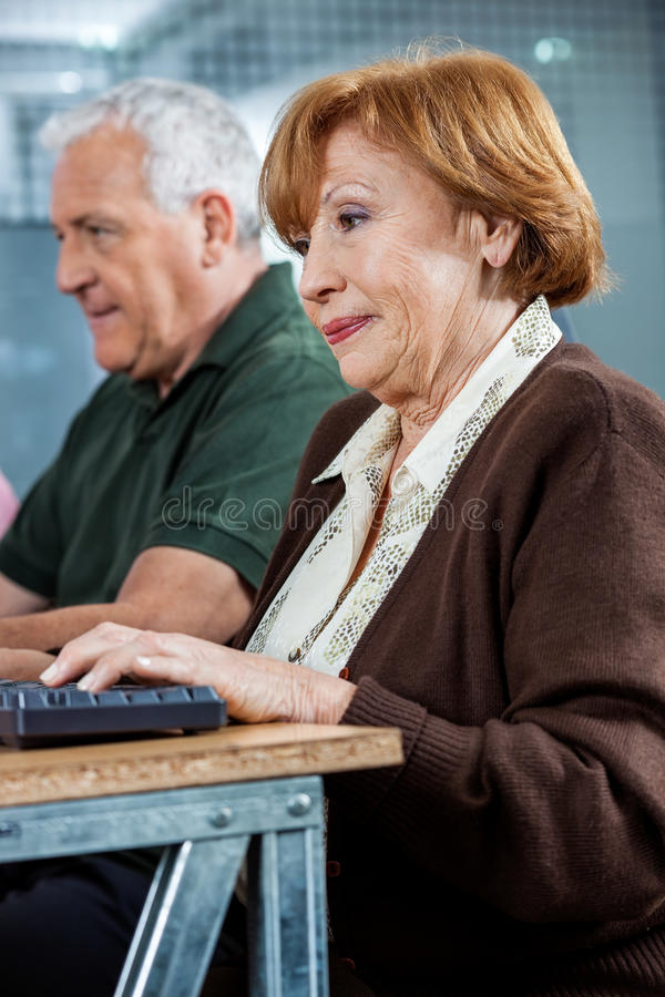 Confident Senior Students Using Computer In Classroom. Confident senior women using computer at desk with classmate in classroom stock image