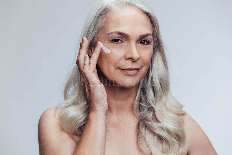 Senior woman applying anti aging face cream royalty free stock image