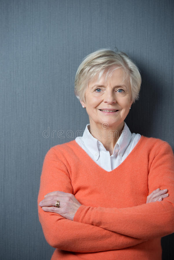 Confident senior woman with folded arms. Confident attractive senior woman with folded arms standing against a dark grey background smiling at the camera royalty free stock photos