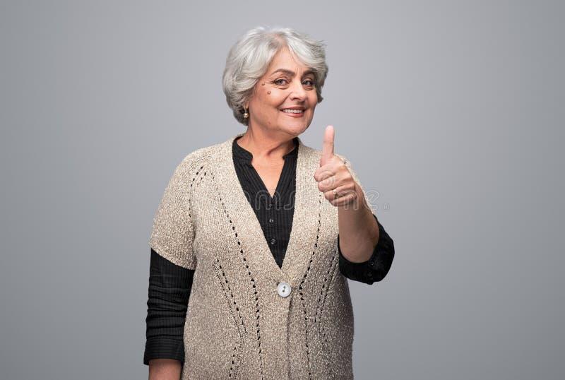 Confident senior woman gesturing thumb up stock photos