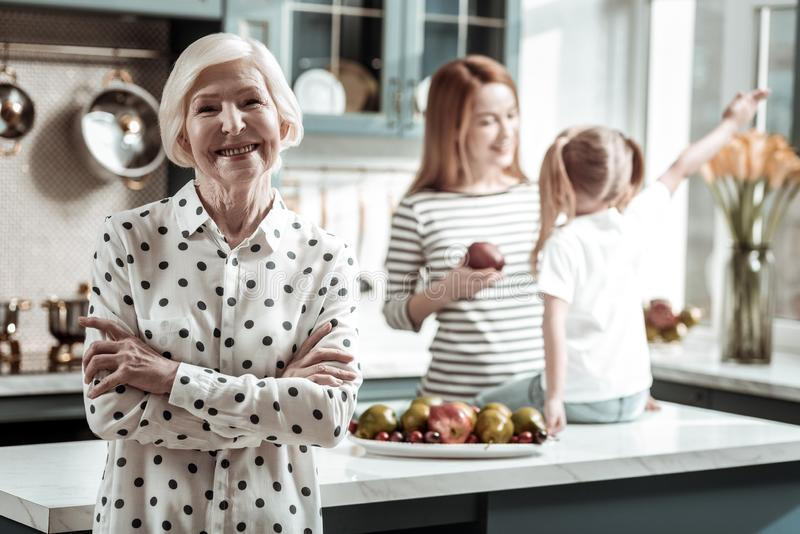 Confident senior woman standing with her arm crossed and smiling while visiting relatives stock images