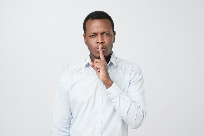 Serious african male keeps index finger on lips, asks not tell his secret to other people. royalty free stock images
