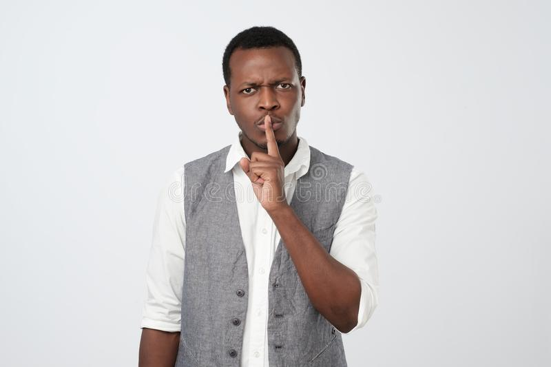 Serious african male keeps index finger on lips, asks not tell his secret to other people. stock photos