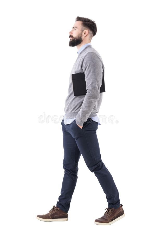 Confident serious businessman walking and carrying planner under arms. Side view royalty free stock images