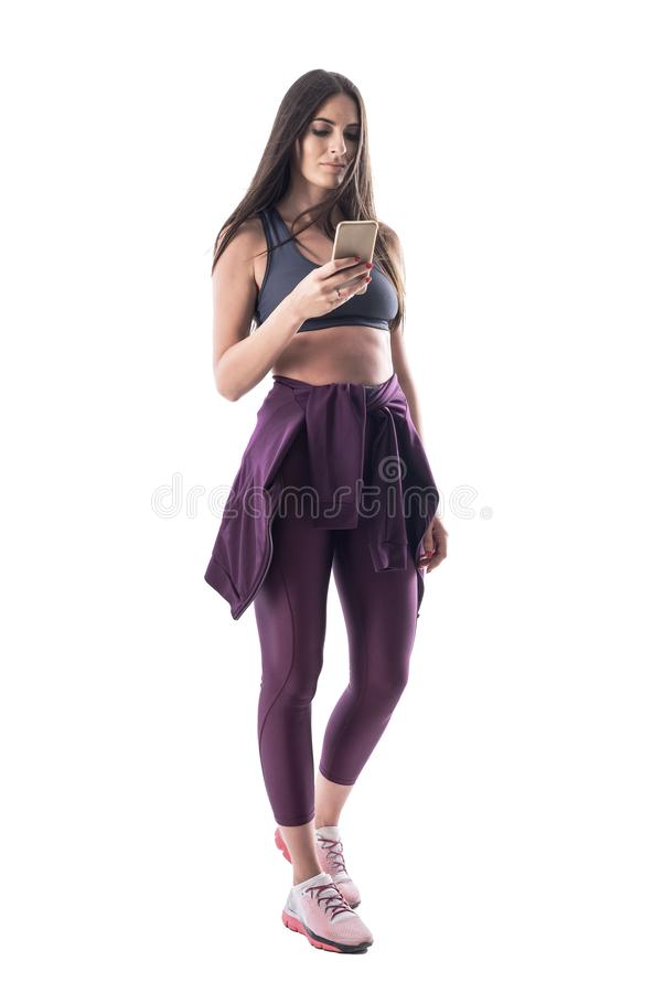 Confident serious fit sporty woman in sports clothes using cellphone royalty free stock images