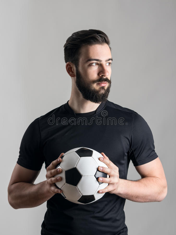 Confident serious football or soccer player intense portrait looking at light source stock photo