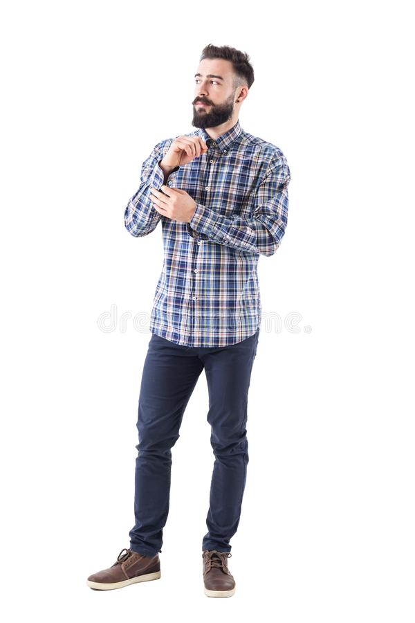 Confident serious macho bearded man buttoning sleeve button getting dressed looking away. royalty free stock photo