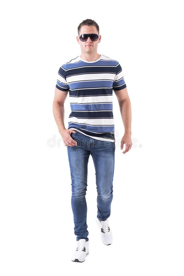 Confident serious macho man with sunglasses and jeans walking towards camera with intense look. Full body isolated on white background stock photo