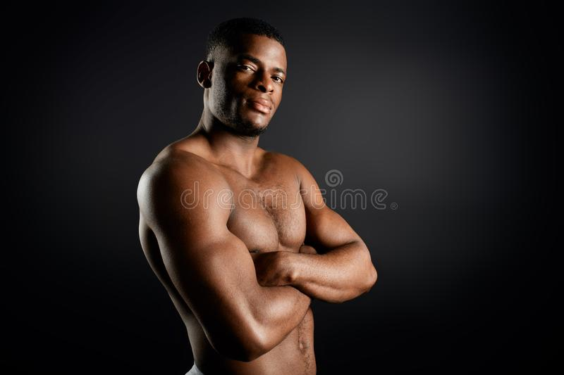 Confident serious personal trainer with folded arms posing to the camera. Isolated black background. confidence concept. copy space stock photos