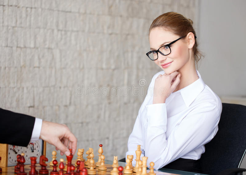 Confident smart businesswoman playing chess and smile. In office, strategy stock photos