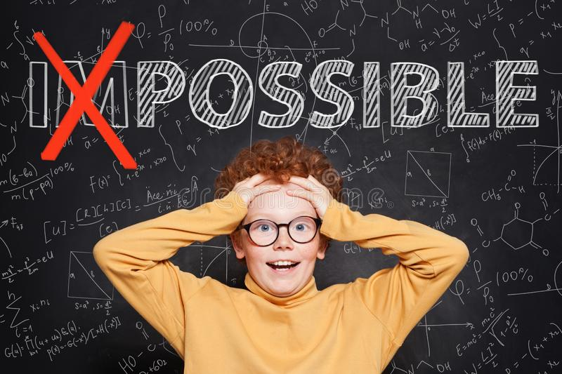 Confident smart kid with text possible on chalkboard background. Success and develop concept royalty free stock photo