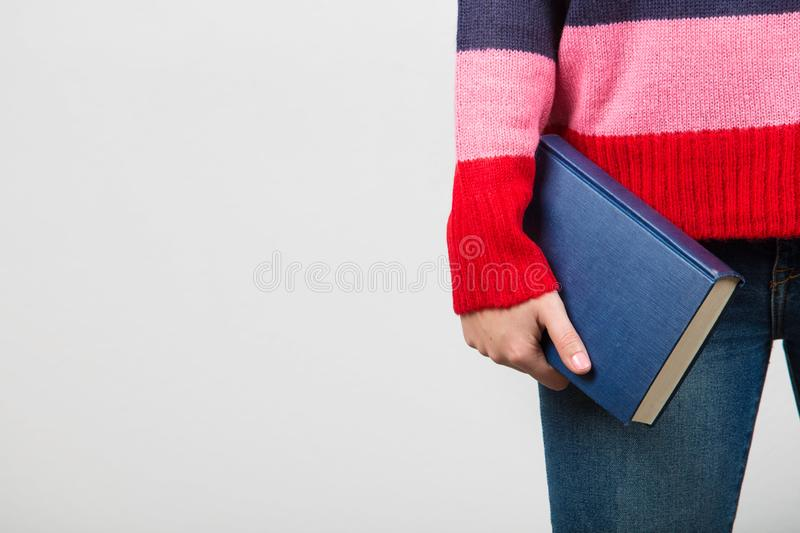 Confident smart student girl holding book in one hand over white background.Close up of a student hand holding.Confident studying stock image