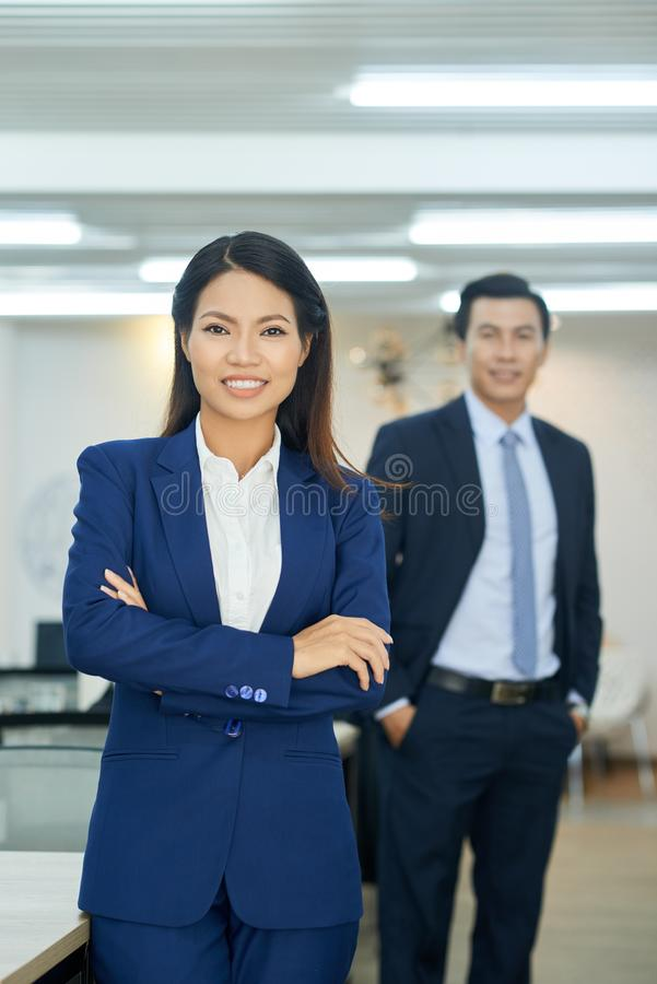 Woman boss. Confident smiling business women and her coworker behind royalty free stock photos
