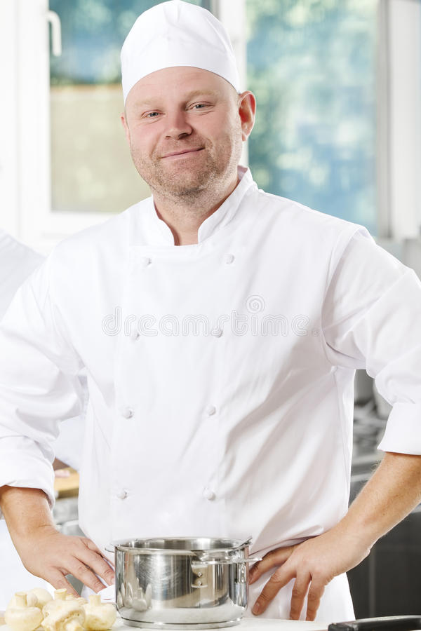 Confident and smiling chef standing in large kitchen royalty free stock photos