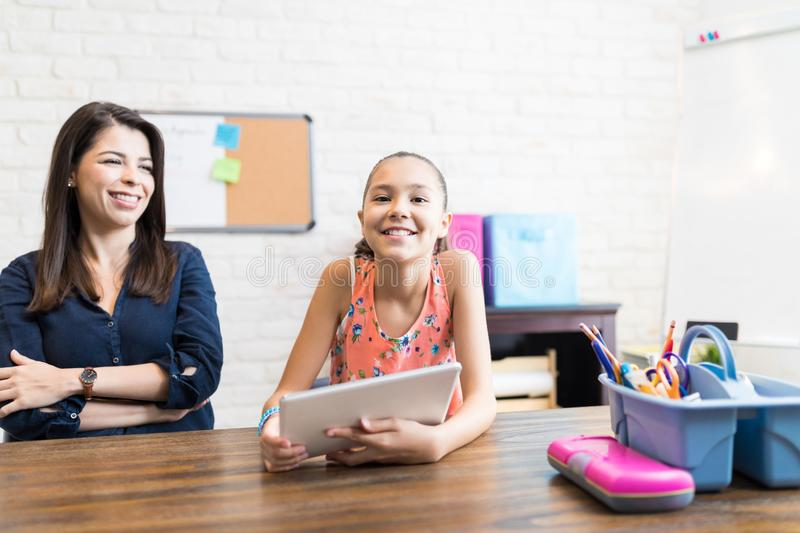 Confident Girl Holding Digital Tablet By Teacher At Table royalty free stock image