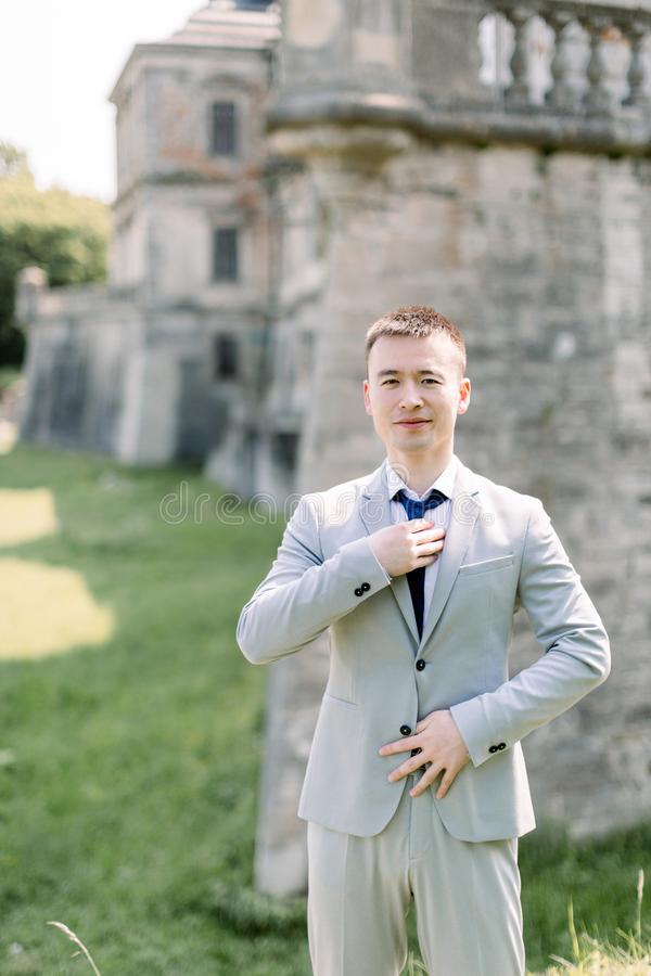 Confident smiling handsome Chinese man groom in gray suit posing on the background of old ancient castle royalty free stock photos