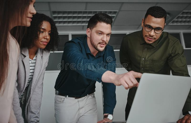 Confident smiling male executive manager explains to his colleagues new online project startup on laptop in the office royalty free stock image