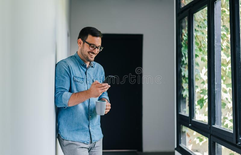Confident smiling young cheerful casual man looking in and using his mobile smart phone satisfied with content drinking coffee stock photos