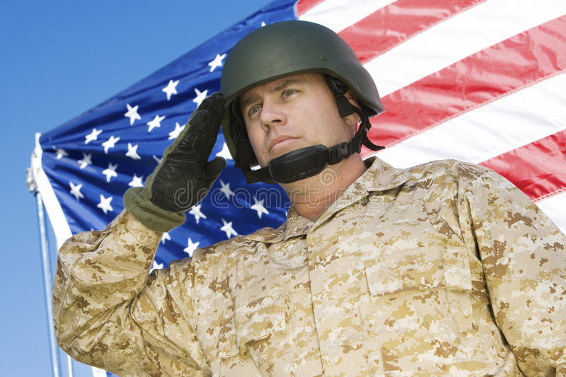 Confident Soldier Saluting In Front Of American Flag. Low angle view of confident soldier saluting in front of American flag royalty free stock photos