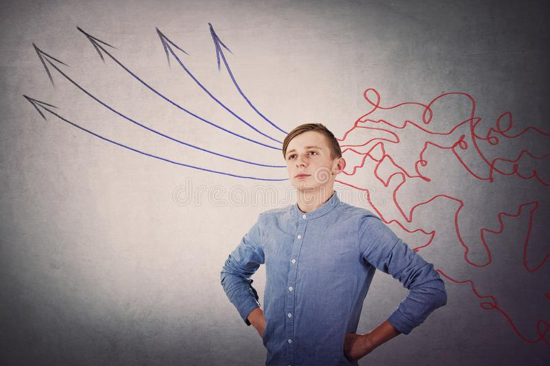 Confident student boy looking up pensive. Concept of information processing, focused teenager transform the mess lines, as royalty free stock photos