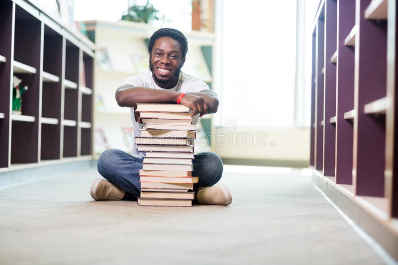 Confident Student With Stacked Books Sitting In royalty free stock photos