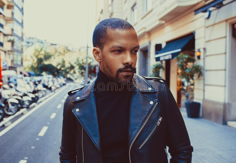 Confident stylish african american man wearing black leather jacket outdoor. Street wear fashion black man royalty free stock images