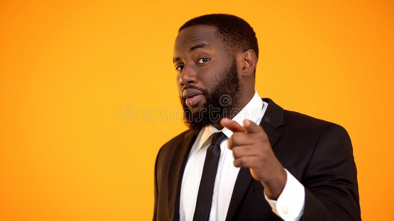 Confident stylish afro-american man in suit pointing with finger, dating site stock photo