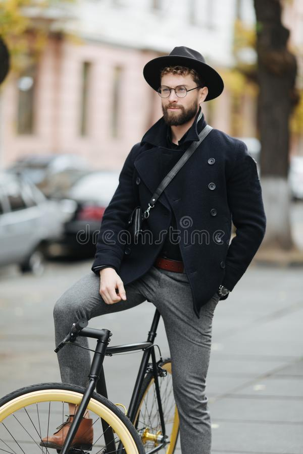 Confident and stylish. Full length of confident young bearded man adjusting eyewear while sitting on his bicycle outdoors. Confident and stylish. Full length of royalty free stock photos