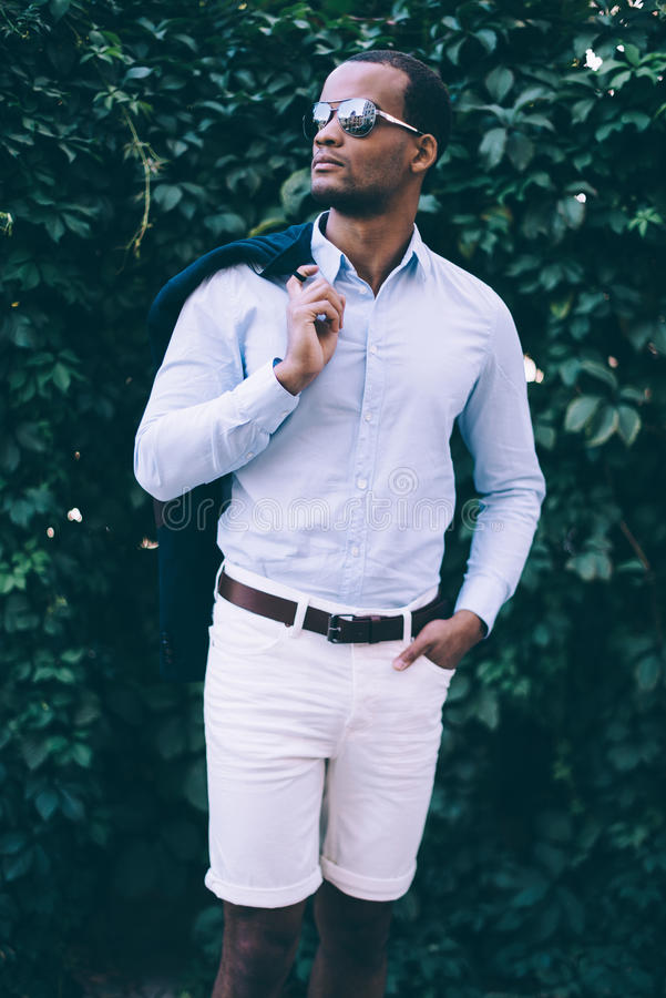 Confident and stylish. Handsome young African man in sunglasses carrying his smart casual jacket on shoulder and looking away while standing against green plant royalty free stock photos