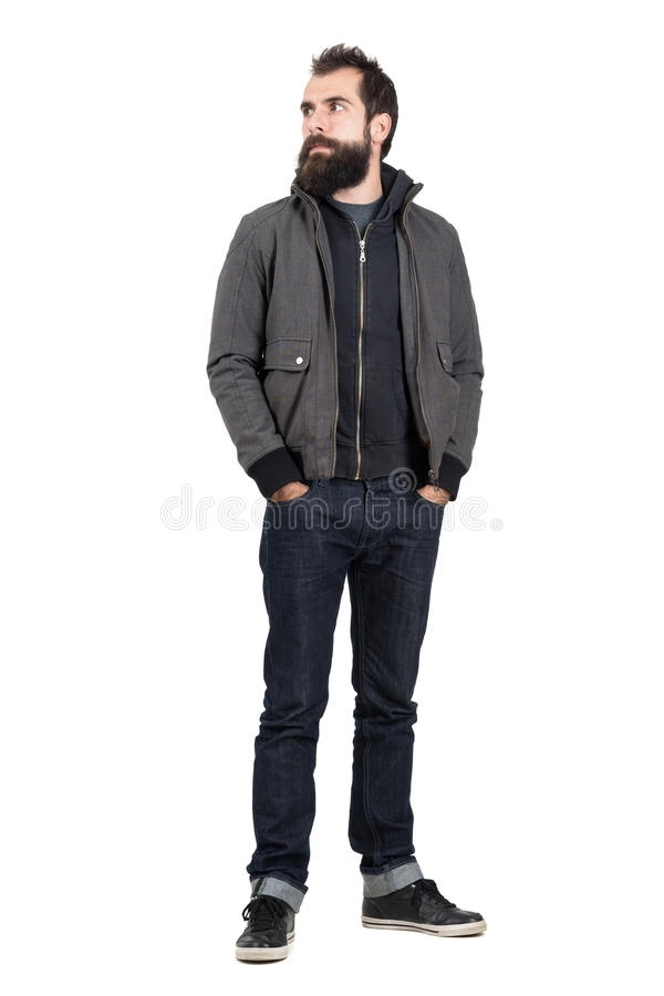 Confident stylish hipster wearing jacket over hooded sweatshirt looking away with hands in pockets stock photography