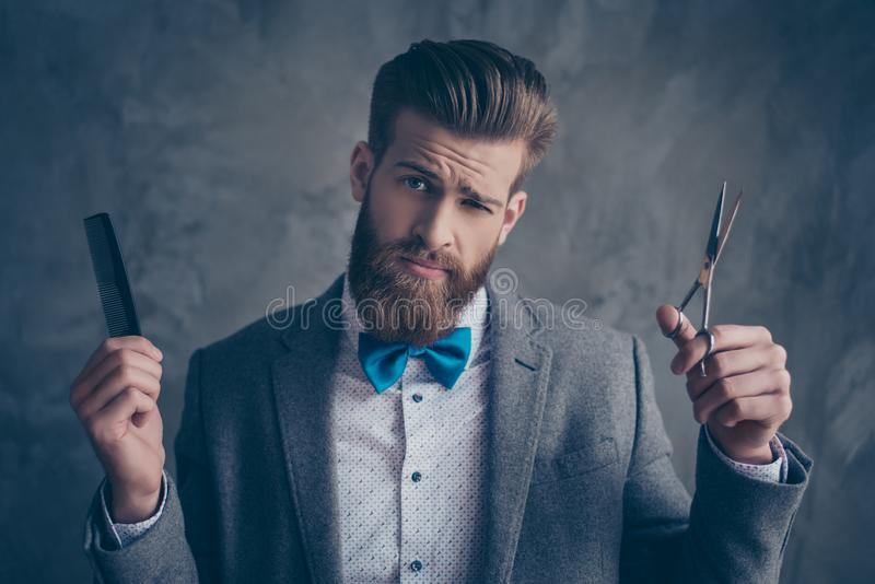 Confident stylish man in suit and bow choosing between scissors stock images