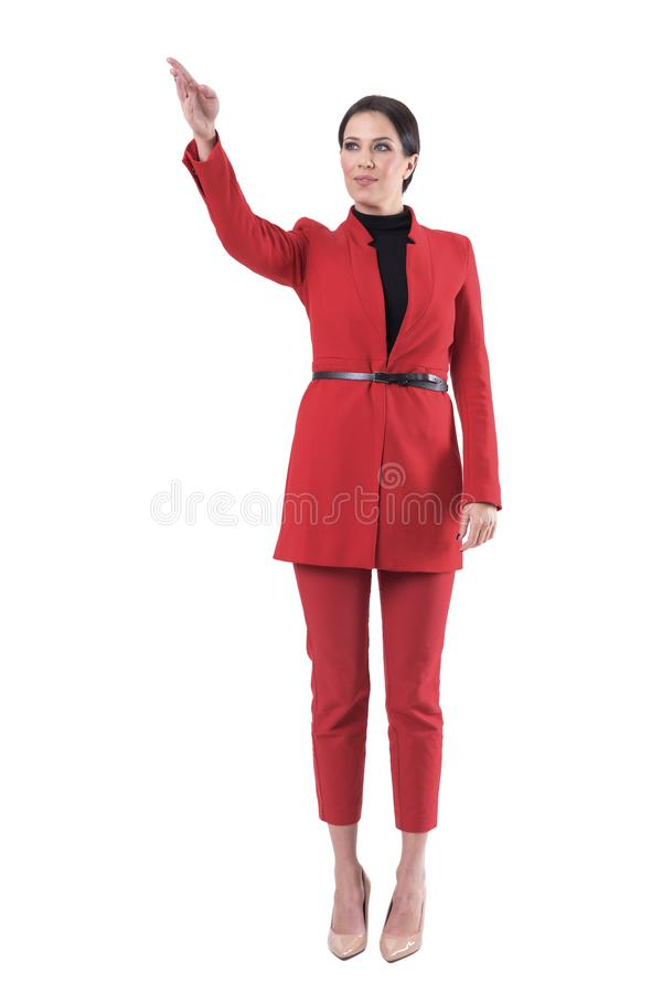 Confident successful business woman in red formal suit showing direction leading the way to success. stock image