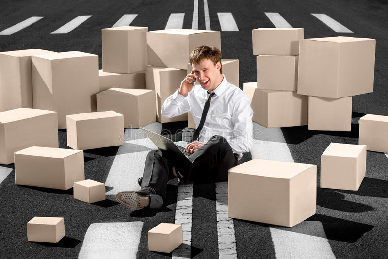 Confident and successful businessman sitting on the road and speaking phone working with laptop surrounded with boxes on the road stock photos