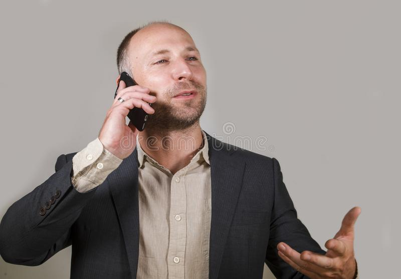 Confident successful businessman talking on mobile phone having business conversation with cellphone smiling cheerful in corporate stock images