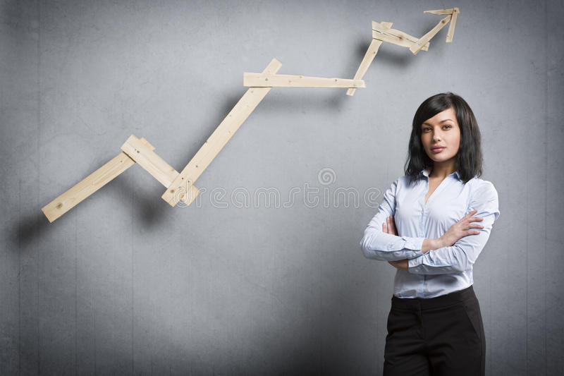 Confident successful businesswoman in front of positive trend chart. Concept: Positive business outlook. Smiling confident businesswoman in front of business stock photography