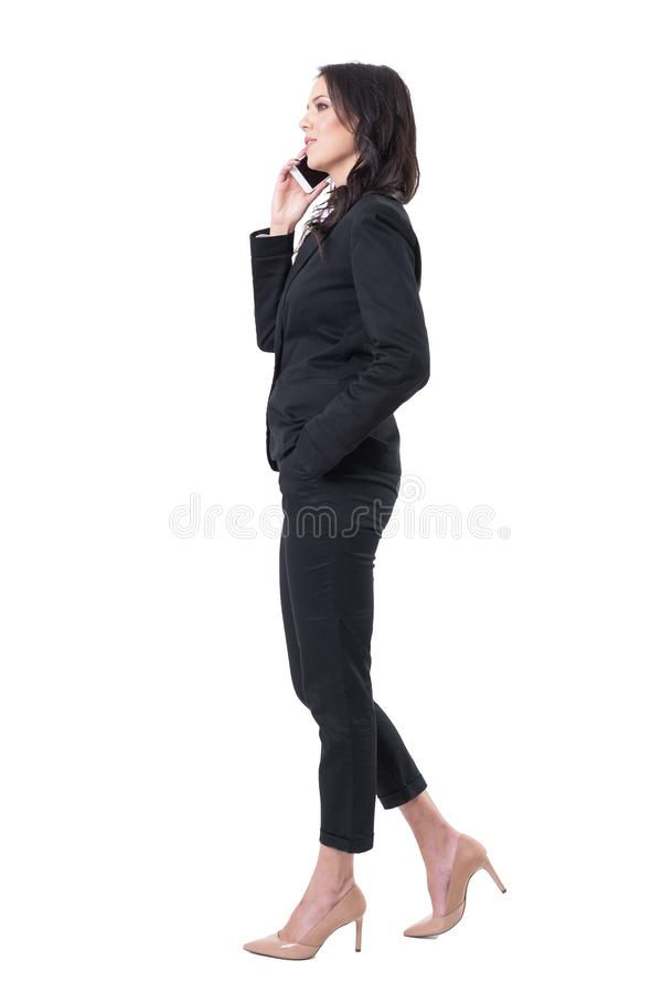 Confident successful female business manager in suit talking on the cellphone. Side view. stock images