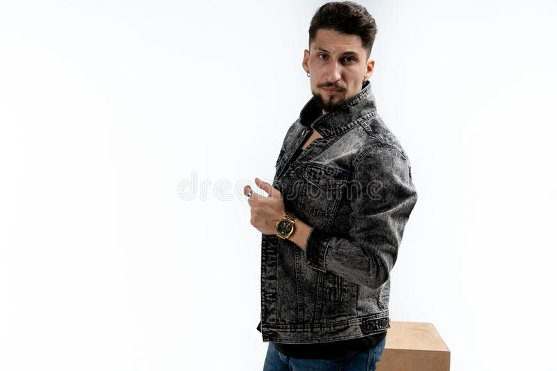 Confident and successful. Handsome young bearded man in denim shirt, looking at the camera, isolated over white stock image