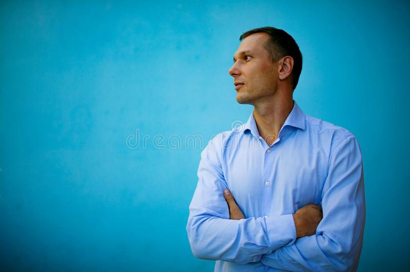 A confident handsome young man standing in front of a blue background. royalty free stock photography