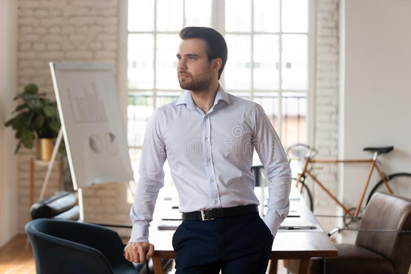 Confident successful male millennial company owner thinking of business growth. royalty free stock image