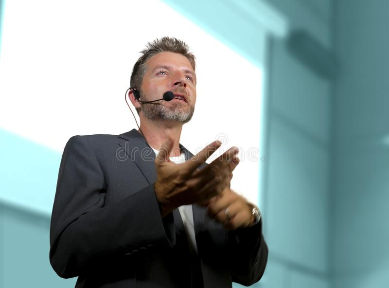 Confident successful man with headset speaking at corporate business coaching and training auditorium conference room talking. Young attractive and confident royalty free stock image