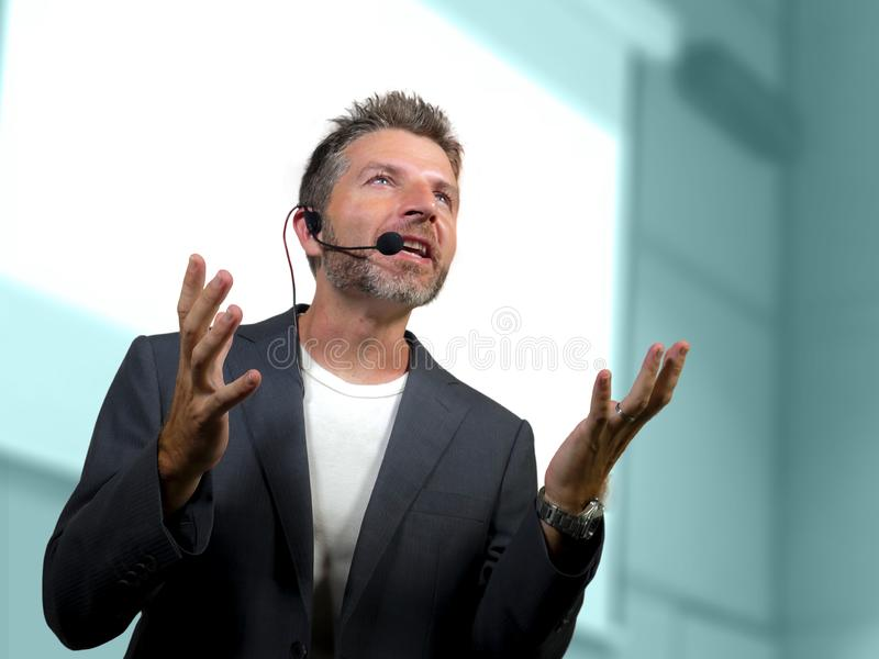Confident successful man with headset speaking at corporate business coaching and training auditorium conference room talking. Young attractive and confident royalty free stock photo