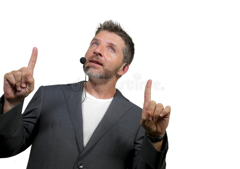 Confident successful man with headset speaking at corporate business coaching and training auditorium conference room talking. Young attractive and confident stock photography