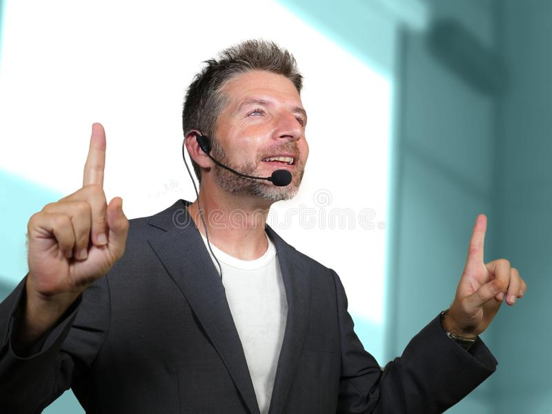 Confident successful man with headset speaking at corporate business coaching and training auditorium conference room talking. Young attractive and confident royalty free stock photography