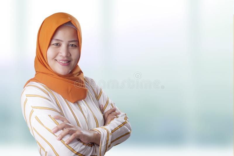 Confident Successful Muslim Lady Smiling Friendly. Successfull happy Asian muslim woman wearing hijab smiling friendly with arms crossed, confident strong stock images