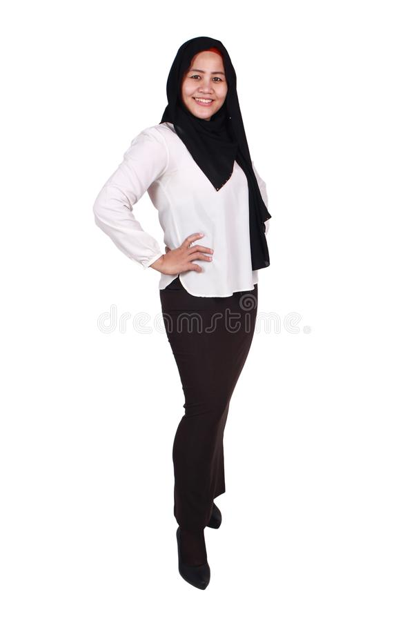 Confident Successful Muslim Lady Smiling Friendly. Successfull happy Asian muslim woman wearing hijab smiling friendly with hands on hips, confident strong royalty free stock image