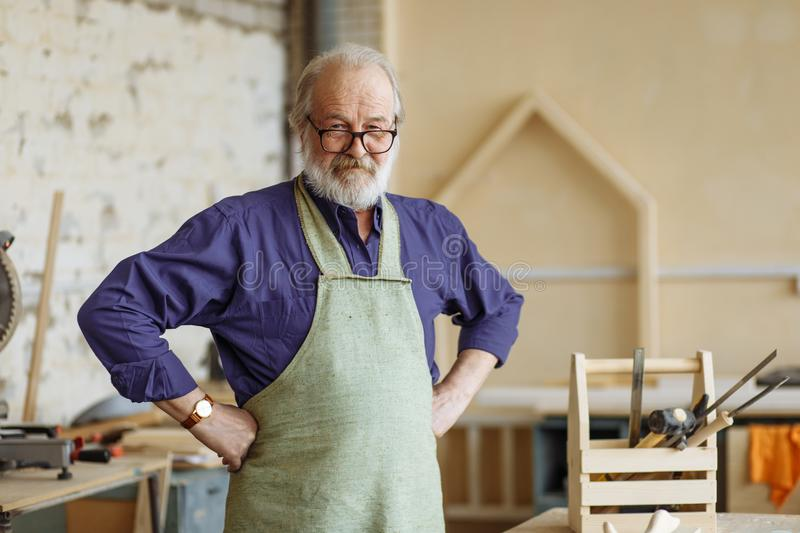 Confident and successful old grey haired man with hands on the hips. At workplace stock image